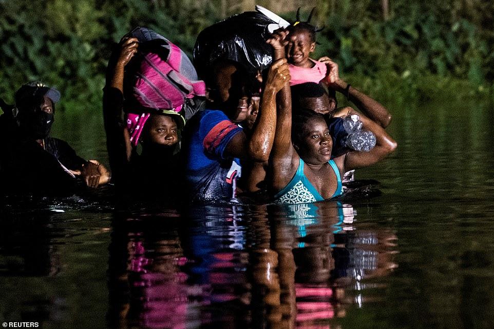 Migrants seeking asylum cross the Rio Grande river into the U.S. on Thursday night