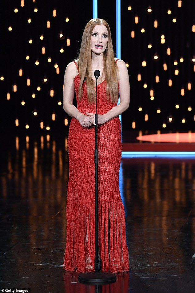 Ruby Red: She wore a floor-length red gown with a taut asymmetric hem while standing on stage at the ceremony