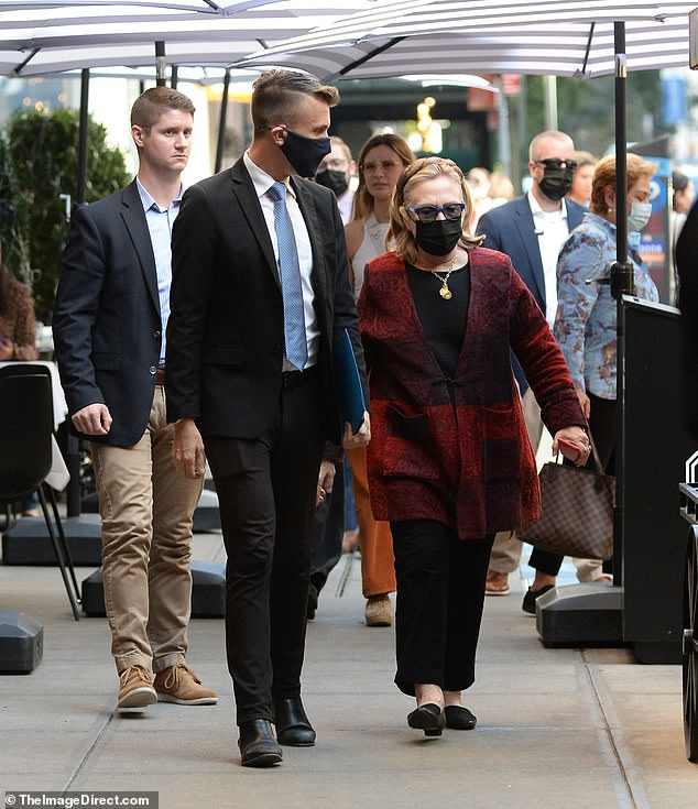 Mrs Clinton was directed to her seat by the restaurant's maitre'd while several Secret Service agents could be see in tow
