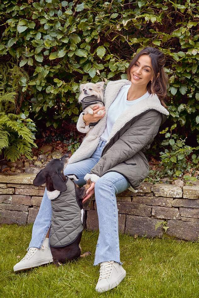 Pooch: For a different look, she wore a khaki wool-lined parker, a white t-shirt and light denim jeans as she snuggled up against a sausage dog