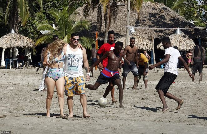Photographs show brief moments of normalcy as Haitian migrants try to make their way to the United States. Tourists are seen wondering about a Colombian beach as migrants play soccer while they wait to embark for the dangerous Darien jungle