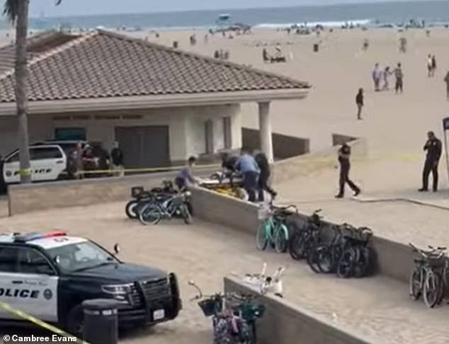 Witnesses say three police officers were pursuing a man in a white t-shirt and jean shorts as he passed under the pier. Police said he had a gun and refused to drop the weapon
