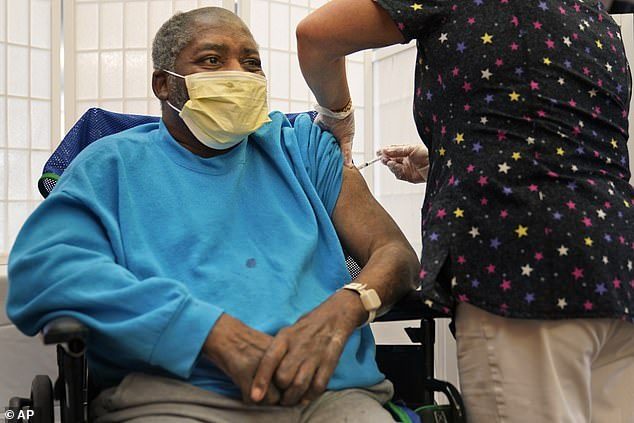 A new poll looked at vaccination rates by political affiliation as well as understanding of vaccine efficacy and COVID-19 hospitalization risk. Pictured:Edward Williams, 62, a resident at Hebrew Home at Riverdale, receives a COVID-19 booster shot in New York, September 27