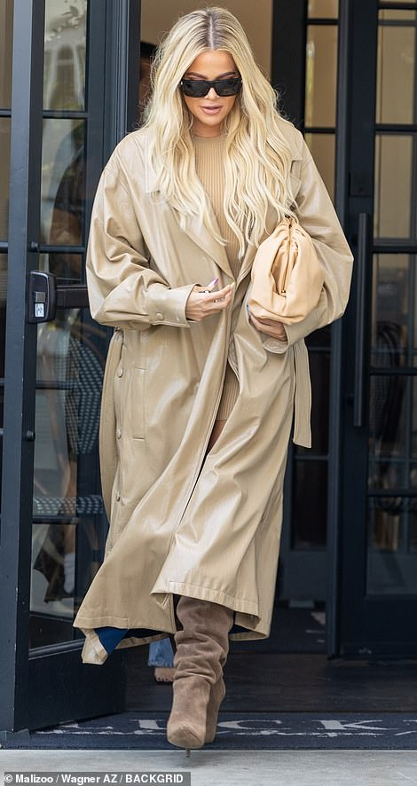 Winter warmer: Khloe opted for a more beige affair as she rocked a long tan trench boat with brown suede boots, all complementing her flowing long blonde locks