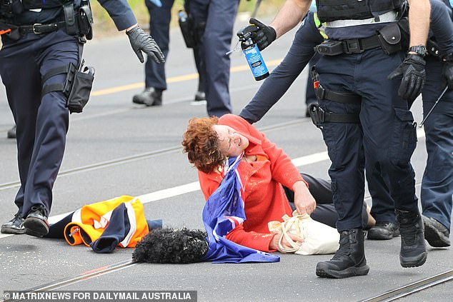 The injured protester is seen writhing in pain as she's helped to her feet by police