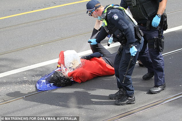 The woman shields her face while being doused with pepper spray by police
