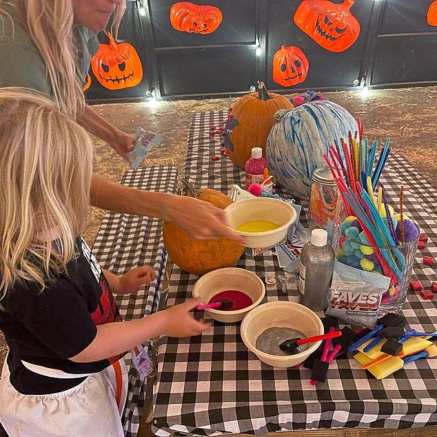 Time to paint: The fashion designer also shared a photo of her son Hendricks painting a pumpkin on a black and white tablecloth