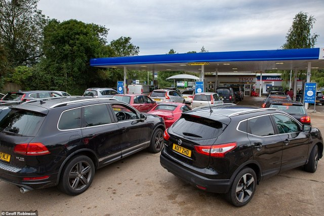 Desperate motorists queue to fuel up at a Tesco in Ely, Cambridgeshire today despite the PM saying the crisis is 'abating'