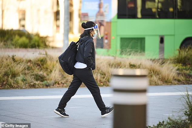 The alarming case is one of 28 new infections recorded in the ACT on Wednesday. Pictured: A pedestrian wearing a face shield walks through Canberra