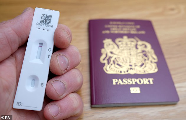 A man holds a negative lateral flow COVID-19 test in front of a UK passport (file picture)