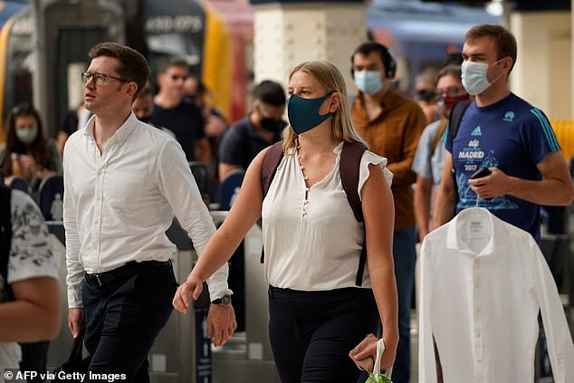 Commuters wearing facemasks arrive at Waterloo station in London on July 19, 2021
