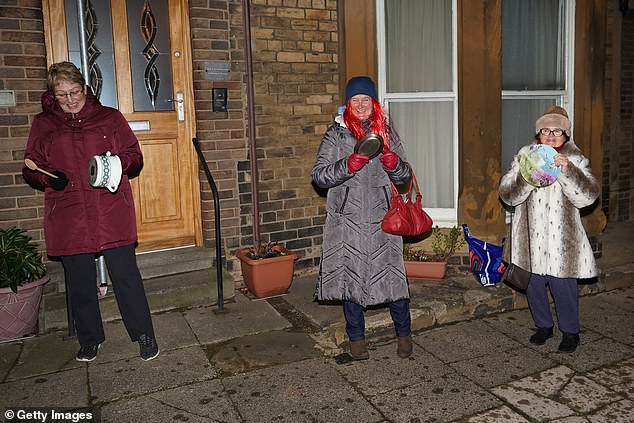Covid has encouraged Brits to get to know their neighbours and improved community spirit, a study has claimed. Pictured:Residents of a street in Saltburn, north Yorkshire, clap for carers in January