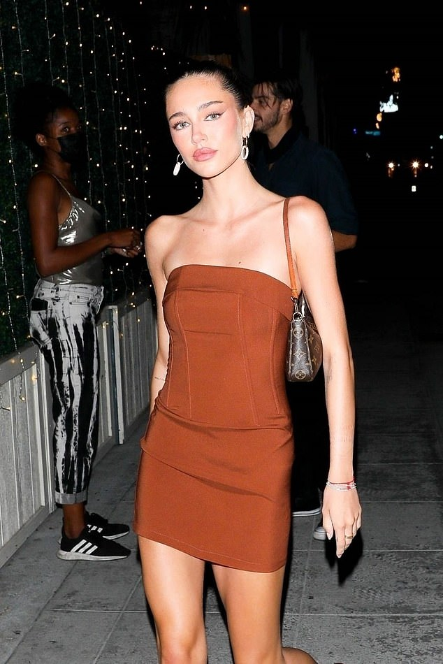 Stunning:The model, 22, wowed in a strapless brown mini dress as she strutted her stuff down the pavement to grab a bite to eat