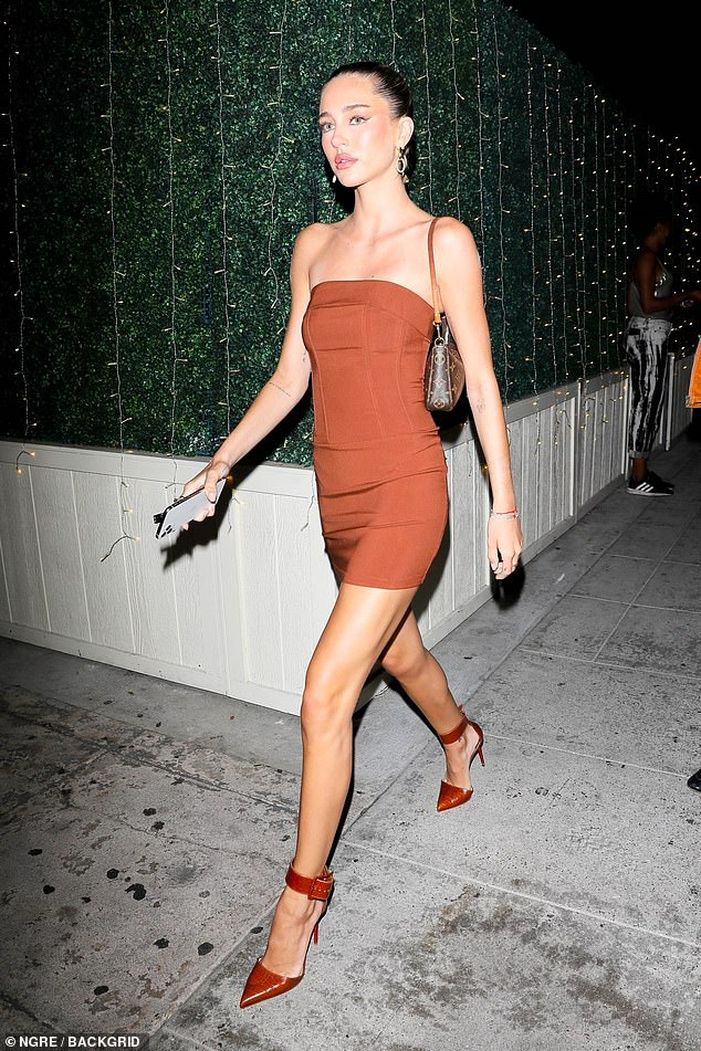 Style:She teamed the thigh-skimming number with strappy heels of the same hue and carried a Louis Vuitton bag over her shoulder