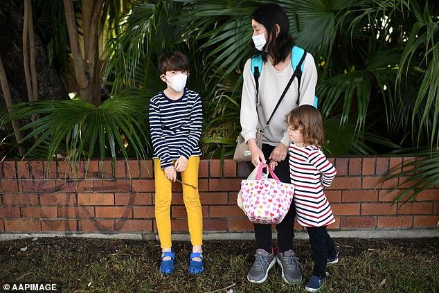 The face mask mandate will be eased, only required to be worn in indoor venues including in schools unless a teacher is addressing the class (pictured: a family queue for a Covid test in Brisbane)