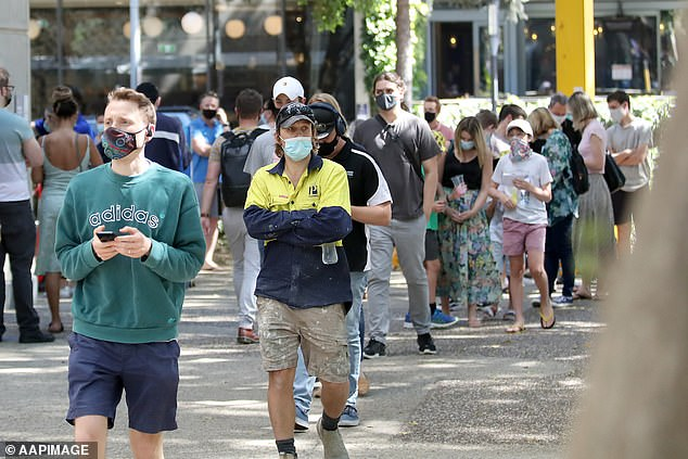The state is set to hit 70 per cent double vaccination target at the end of October to early November (pictured: masses line up for their Covid vaccines at South Bank, Brisbane)