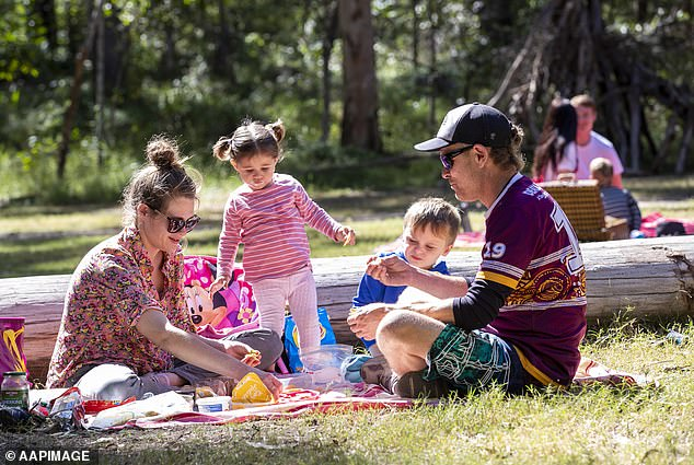 Queenslanders can enjoy additional freedoms from Friday afternoon as the state records zero new Covid cases (pictured: family enjoys a picnic in Brisbane)
