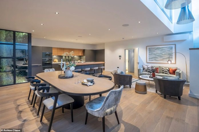Upon entering the home (pictured), the new owner will see a well-designed mezzanine reception, which is finished in muted tones and features a bespoke fitted matte black floor for the ceiling cabinets