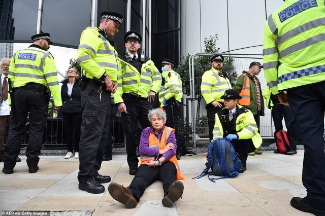 An elderly woman is kept in handcuffs on the pavement by Old Street - one of London's busiest junctions