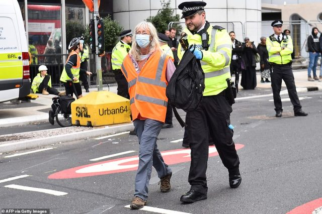 A woman is led away by a police officer, who is carrying her backpack, after Insulate Britain blocked the Old Street roundabout today
