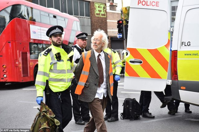 An elderly Insulate Britain protester - wearing a suit and tie - is arrested and taken into a waiting police car by officers