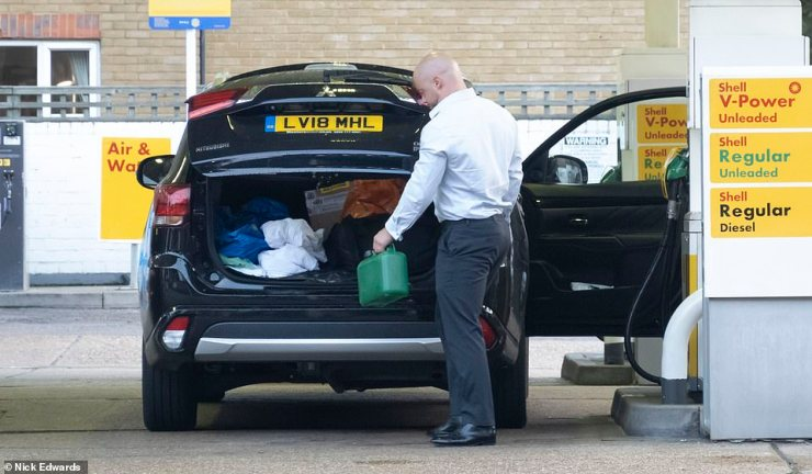 A man is seeing filling a jerry can at a Shell petrol station in South East London today