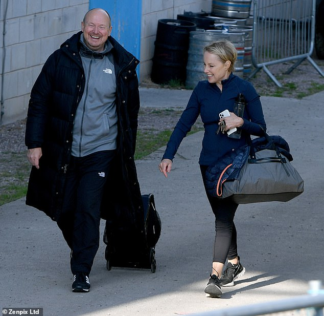Happy: Sally Dienevar appeared in great spirits on Friday with her trainer in a cheerful exit from her local ice rink as she prepared for her stint on Dancing on Ice.