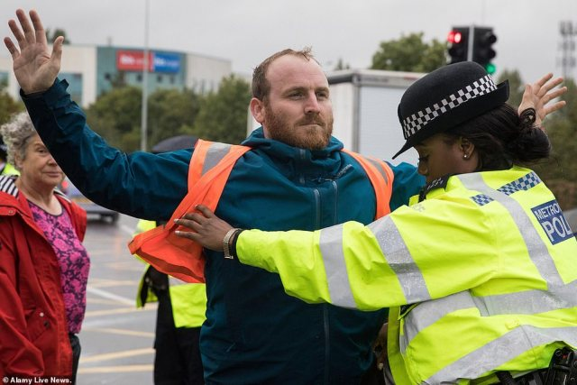 Mr Norton is pictured being arrested after a slip road from the M25 at Junction 14, close to London's Heathrow Airport, was blocked by Insulate Britain on September 27