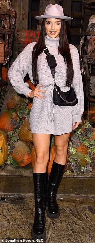Incredible: Emmy Day showed off her bronzed legs in a gray knit minidress, which she paired with a pair of shin-high onyx boots