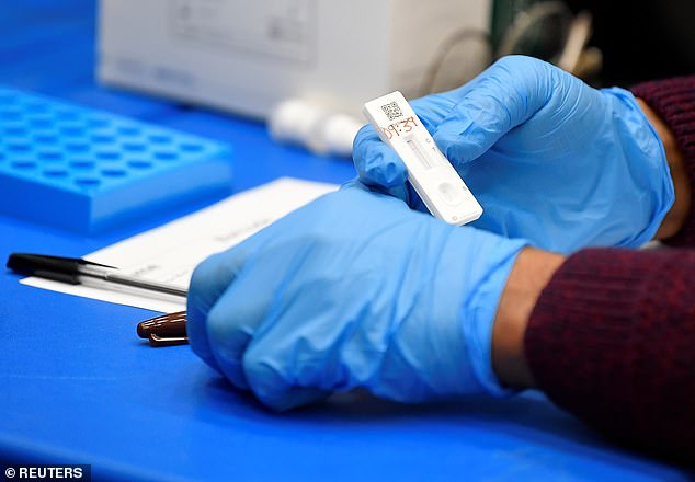 Discussions are being held in Government to scale back the initiative that allows everyone to get a free lateral flow test, and some people a free PCR test, according to The Daily Telegraph. Pictured: A health worker handles a lateral flow samples inBeckenham (file photo)