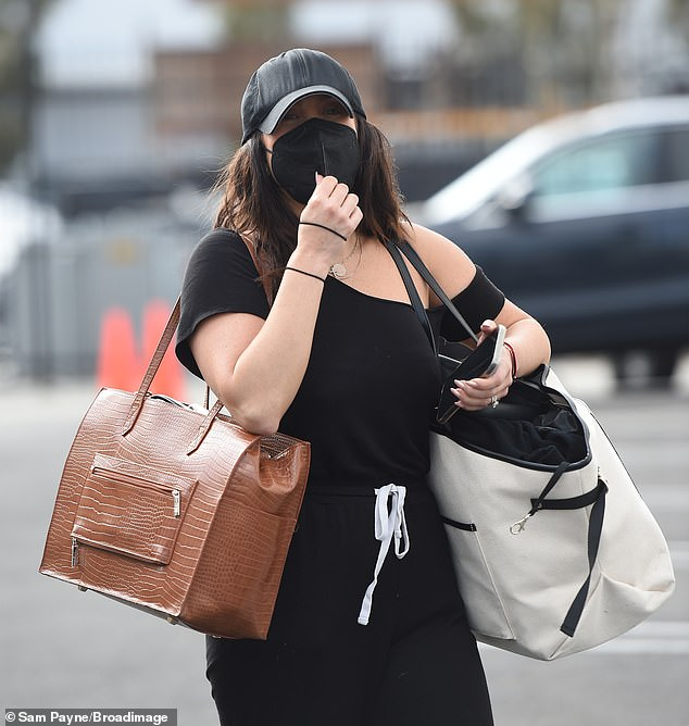 Keeping it casual:For their sweat session, Burke, 37, wore an off-the-shoulder black top, matching sweatpants and a baseball cap