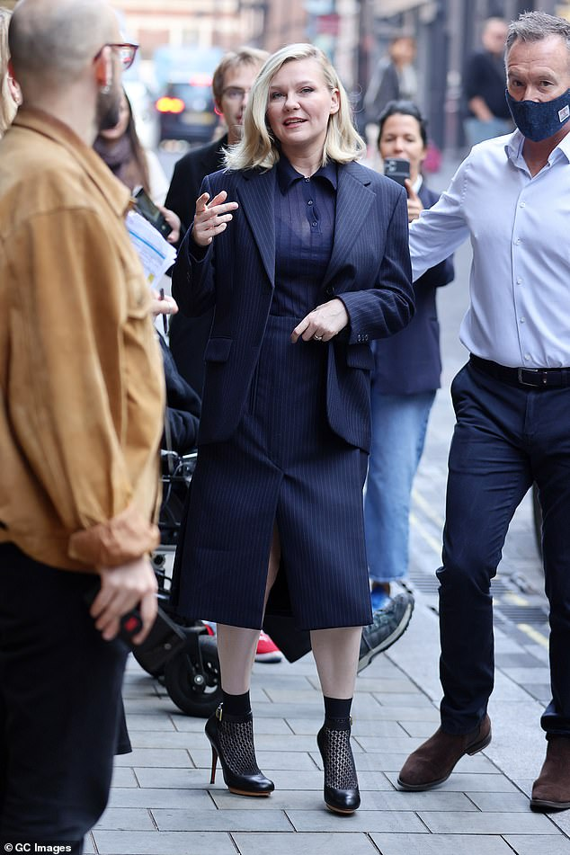 Eye-catching: Kirsten donned a sheer black blouse, a black pinstripe blazer and skirt, and a quirky sock and heel combination