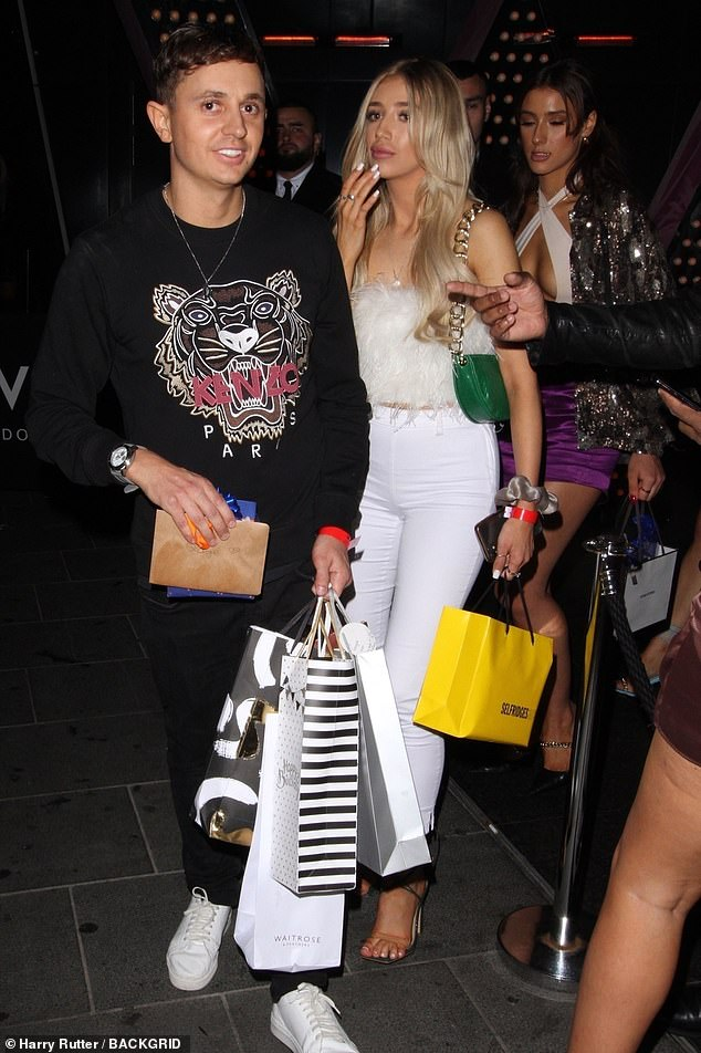 In great spirits: George rocked a casual designer ensemble including a black Kenzo sweater, black jeans, and pristine white sneakers.  He appeared with great enthusiasm as he left the venue with bags of gifts