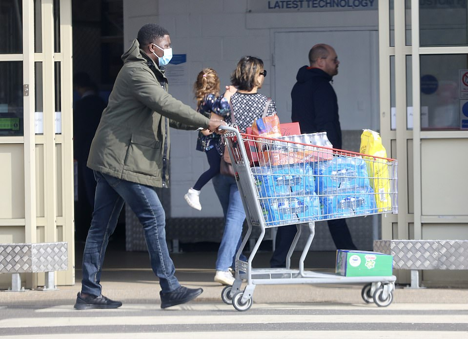 A shopper is pictured pushing a trolley laden with water bottles as he stocks up at a Costco store in Bushey, Hertfordshire