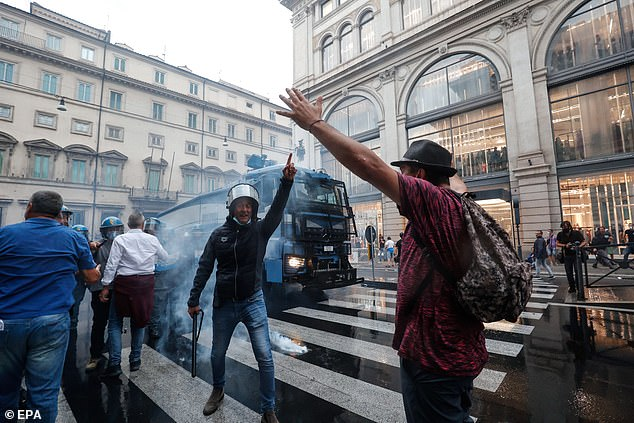"""Policemen use water cannon during clashes between the Police and the """"No Green Pass"""" protesters in the centre of Rome"""