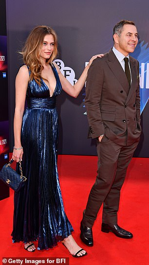 His companion sent temperatures soaring as she flashed her ample assets in a glossy blue maxi dress featuring a tantalising thigh-slit