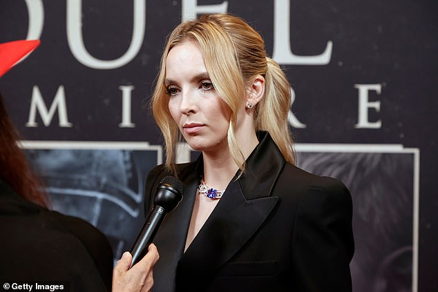 Accessories: The green-eyed stunner wore a diamond-encrusted chain link choker with violet stones around her neck. Diamond stud earrings sparkled in her ears