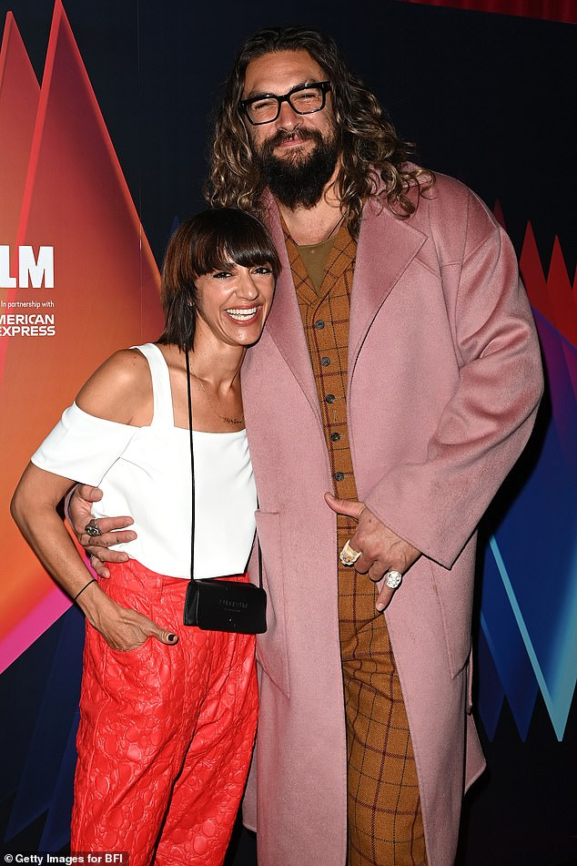Good spirits: Jason opted for a brown checkered suit and a long pink jacket andLily looked glamorous in red tapered trousers and a white cold shoulder blouse