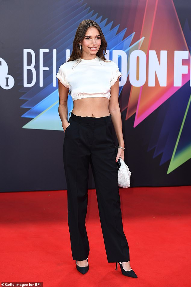 Effortlessly chic: The model looked sensational in a crisp white cropped top that showcased her enviable physique as she arrived for the red carpet event