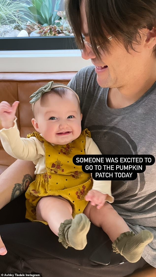 Excited baby:Christopher was shown in a snap with six-month-old Jupiter Iris who beamed while sitting in her father's lap