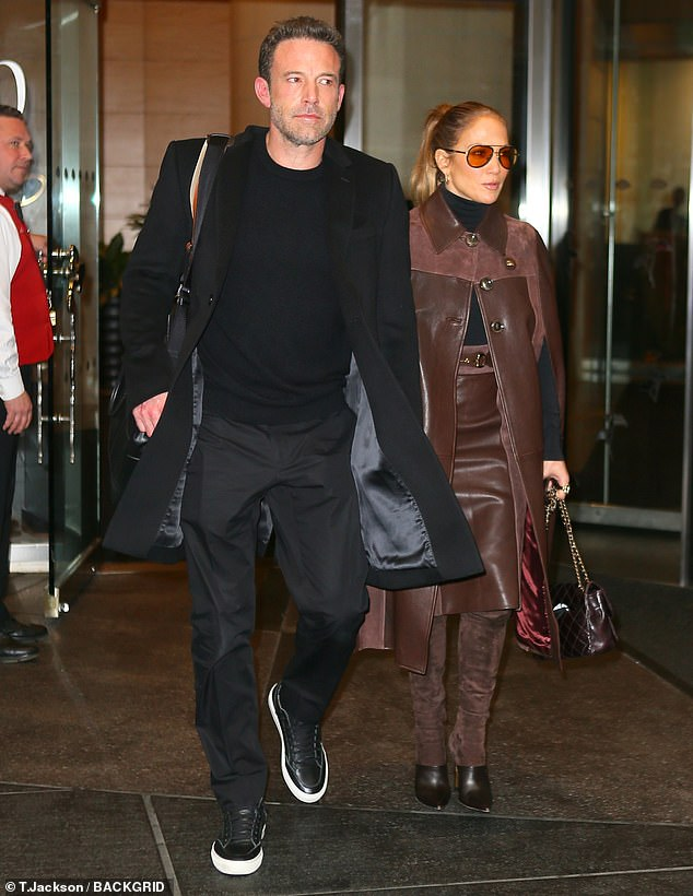 Earth tones: Jennifer's striking coordinated look was built around a chic brown leather cape coat with suede panels around her shoulders and a red satin liner