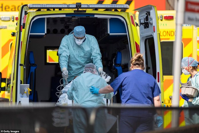 The report also found that the UK¿s response was too ¿narrowly and inflexibly based on a flu model¿ that failed to learn lessons from Sars, Mers and Ebola. Pictured:NHS workers in PPE take a patient at St Thomas' Hospital on April 10, 2020 in London