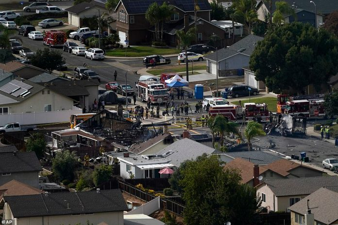 Emergency crews work a the scene of a small plane crash on Monday afternoon which completely destroyed two homes