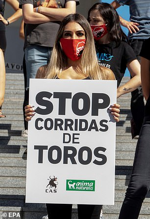 An activist holds a banner reading 'Stop Bullfighting' as people protest against bullfighting at Plaza de la Encarnacion in Seville this September. The rally called for bullfighting to be banned and its public funding stopped
