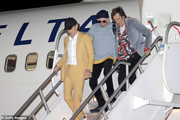 Touring: Taking off from a Delta plane, Mick's flying attire was arguably the most extravagant, as he wore a bold, mustard-colored suit.
