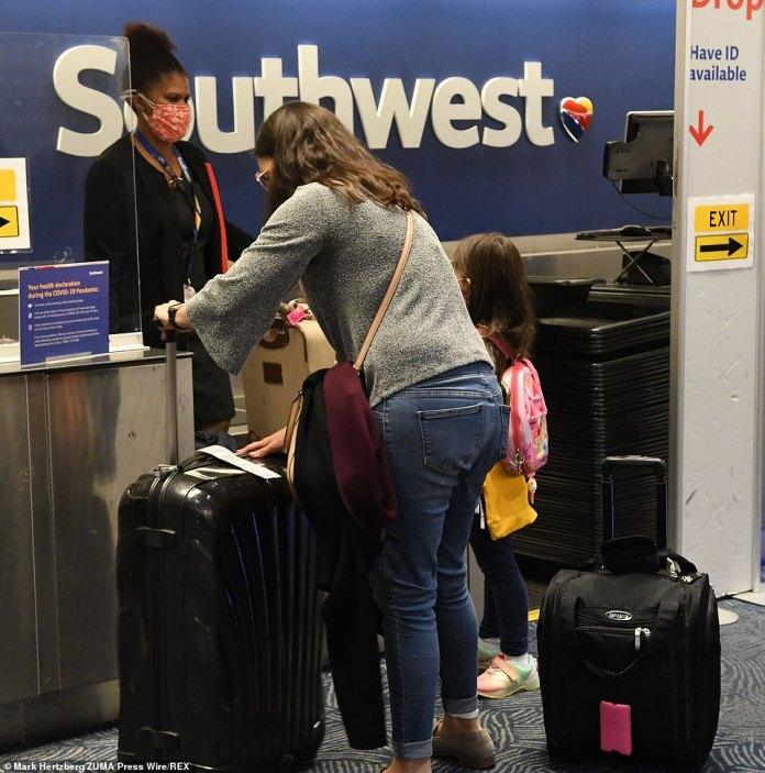 A woman and a child wait to check in at the Southwest terminal at General Mitchell International Airport in Milwaukee on Monday