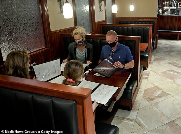 Researchers found that people who were financially conservative or had low fear of the virus were most likely to eat at a restaurant indoors during the pandemic.  Those who were more educated or of higher socioeconomic status were most likely to fly.  Pictured: A family wears masks as they look at a restaurant menu in Amityville, Pennsylvania, July 16, 2020