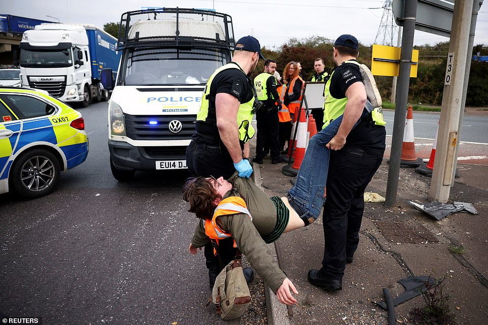 Police officers carry away a man as Insulate Britain activists block the M25 slip road today