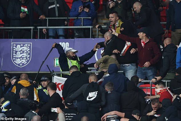 A police offer strikes a Hungary fan in the stands as police try to keep them calm at Wembley