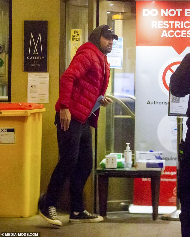 Laid-back: The unshaven athlete dressed for comfort, layering a black hoodie beneath his puffer jacket and a matching baseball cap